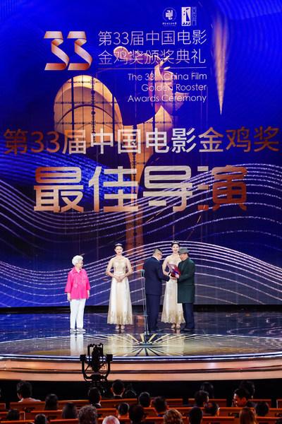 王瑞导演从中国著名女演员田华、中国著名导演李前宽手中接过最佳导演奖的奖杯和证书