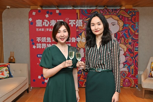 艾克商务中心北京总经理胡雯(右)与艺术家罗晶晶(左)举杯祝贺开幕展完满成功