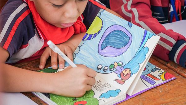 云南乡村学校的孩子正在为手绘书配上文字