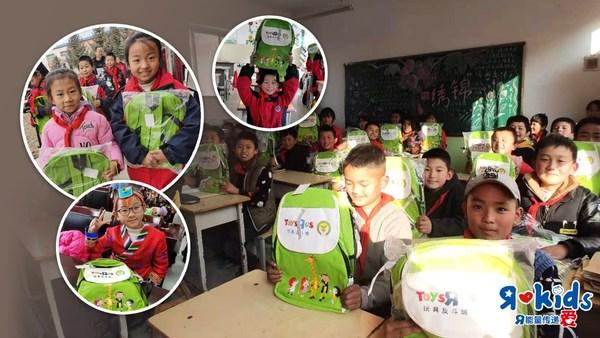 孩子们在收到玩具反斗城的爱心书包后露出了灿烂的笑容,校园里处处洋溢着欢乐和喜悦