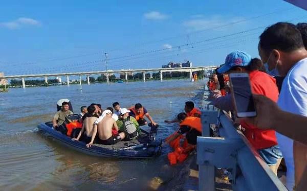 救援队员用皮筏艇运送受灾群众