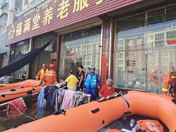 救援队员在河南卫辉市福满堂养老服务中心营救被困老人